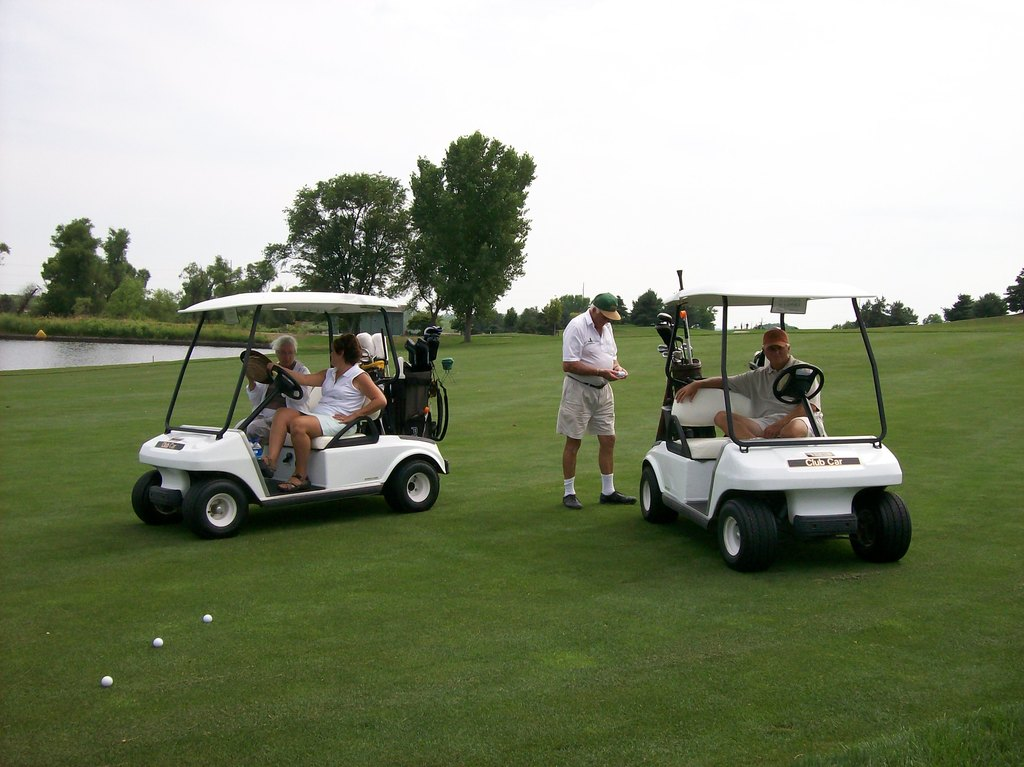 Golf carts with people golfing